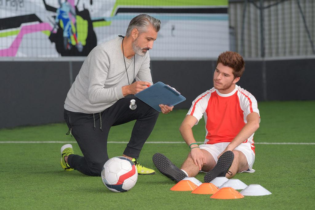 man training a footballer player on football field